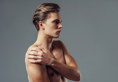 Handsome young man isolated. Portrait of shirtless muscular man is standing on grey background. Man holding his shoulder. Experiencing shoulder pain.