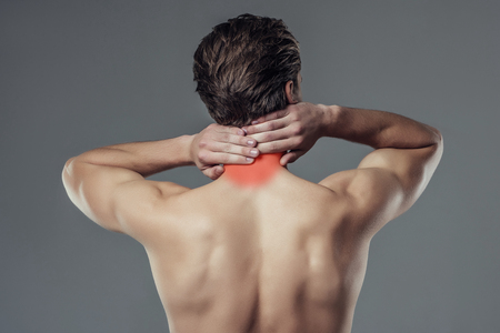 Handsome young man isolated. Shirtless muscular man is standing on grey background. Back view of man holding his neck. Experiencing neck pain.