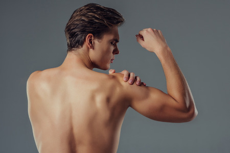 Handsome young man isolated. Shirtless muscular man is standing on grey background. Back view of man holding his shoulder. Experiencing shoulder pain.