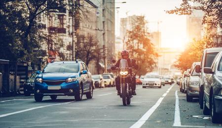Motorfiets en auto's rijden op straat. Stad tijdens de zonsondergang.