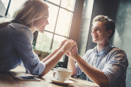 Handsome young man and attractive young woman are spending time together. Romantic couple in cafe is drinking coffee, holding hands and enjoying being together. Foto de archivo