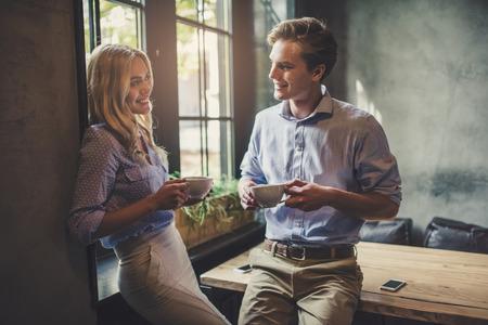 Apuesto joven y atractiva mujer joven están pasando tiempo juntos. La pareja romántica en la cafetería está bebiendo café y disfrutando de estar juntos. Foto de archivo - 91837091