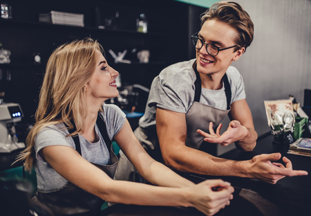 Couple of barista are working in cafe. Handsome man and attractive woman are making coffee. Stockfoto