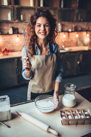 De aantrekkelijke jonge vrouw kookt op keuken. Plezier maken tijdens het maken van cakes en koekjes. glimlachen en kijken naar camera.