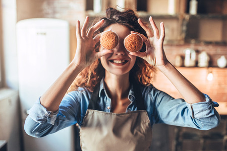 Attractive young woman is cooking on kitchen. Having fun while making cakes and cookies. Standard-Bild