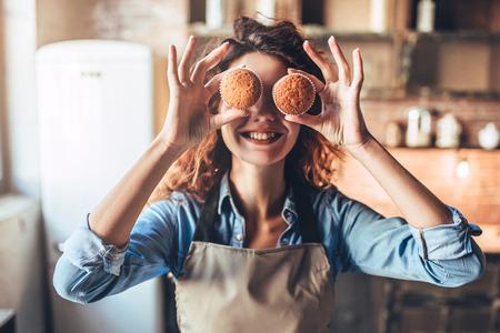 La giovane donna attraente sta cucinando sulla cucina. Divertirsi mentre si fanno torte e biscotti. Archivio Fotografico - 91905976