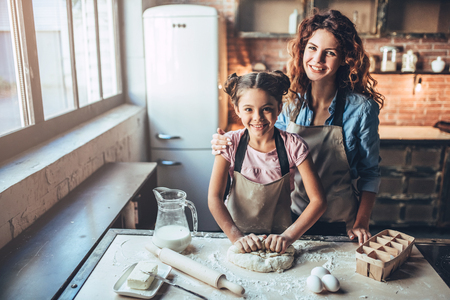 Attractive young woman and her little cute daughter are cooking on kitchen. Having fun together while making cakes and cookies. Smiling and looking at camera. Standard-Bild