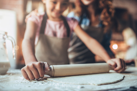 Cropped image of attractive young woman and her little cute daughter are cooking on kitchen. Having fun together while making cakes and cookies. Stok Fotoğraf