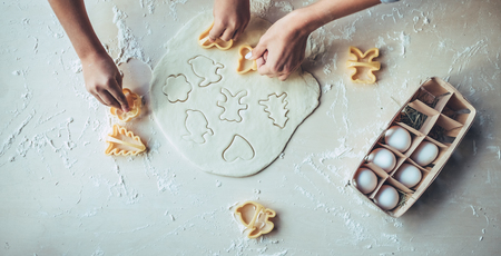 Cropped image of attractive young woman and her little cute daughter are cooking on kitchen. Having fun together while making cakes and cookies. Stock Photo - 91906196