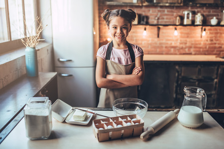 Little cute girl is cooking on kitchen. Having fun while making cakes and cookies. Smiling and looking at camera.