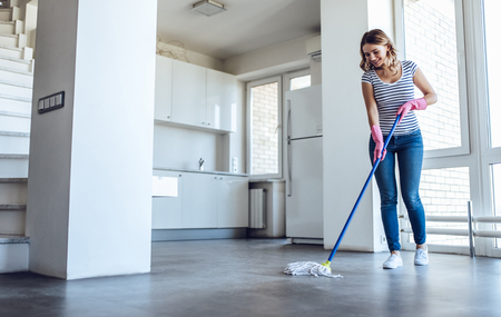 Attractive young woman is washing floor while doing cleaning at home Stock Photo