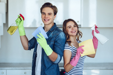 Young happy couple is washing kitchen while doing cleaning at home.