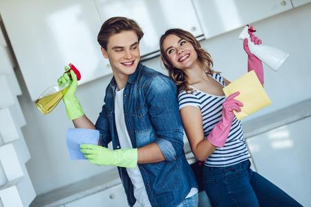 若い幸せなカップルは、自宅で掃除をしながら台所を洗っています。