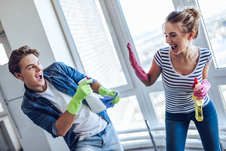 Young happy couple is having fun while doing cleaning at home. Archivio Fotografico