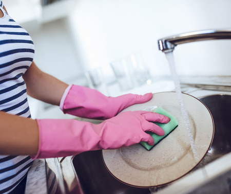 Cropped image of attractive young woman is washing dishes while doing cleaning at home