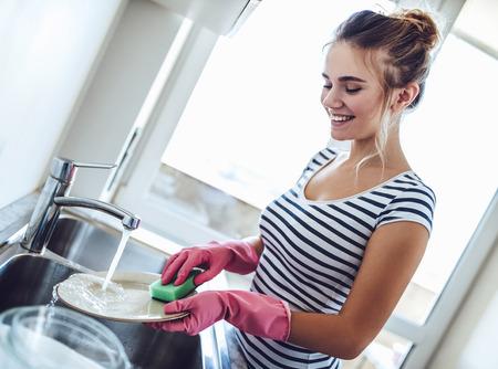 Mulher jovem e atraente é lavar a louça ao fazer a limpeza em casa