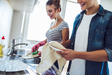 Cropped image of young happy couple is washing dishes while doing cleaning at home. Reklamní fotografie - 91906748