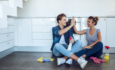 Young happy couple is having rest after doing cleaning at home. Stockfoto