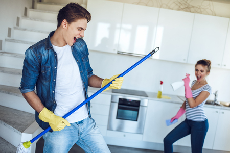 Young happy couple is having fun while doing cleaning at home. Stockfoto