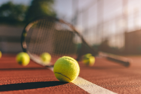 Balls and racket are lying on brown tennis court. Stockfoto