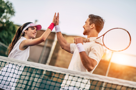 Young couple on tennis court. Handsome man and attractive woman are playing tennis. Giving five.