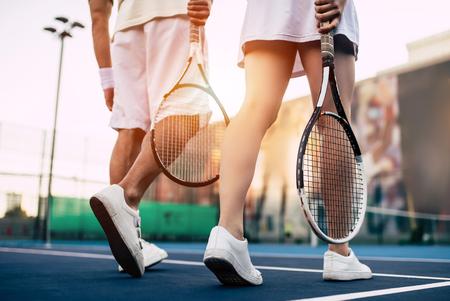 Imagen recortada de la joven pareja en la cancha de tenis. Hombre guapo y atractiva mujer están jugando tenis. Foto de archivo