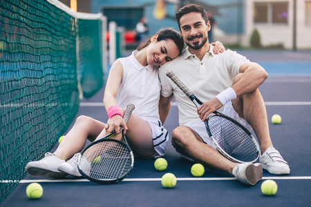 Young couple is sitting on tennis court. Handsome man and attractive woman are playing tennis. Foto de archivo