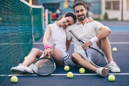 O par novo está sentando-se no campo de tênis. Homem bonito e atraente mulher estão jogando tênis. Foto de archivo - 91996713