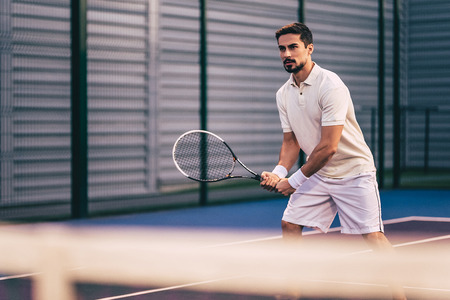Handsome man on tennis court. Young male tennis player.