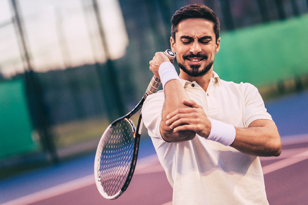 Uomo bello sul campo da tennis. Giovane tennista. Dolore al gomito Archivio Fotografico