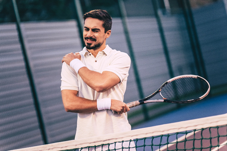 Handsome man on tennis court. Young tennis player. Shoulder pain Archivio Fotografico