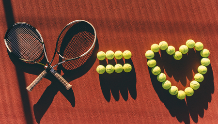 Balls and racket are lying on brown tennis court. I love tennis.