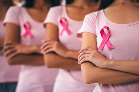Cropped image of group of young multiracial woman with pink ribbons are struggling against breast cancer. Breast cancer awareness concept.