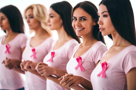 ピンクのリボンを持つ若い多民族女性のグループは、乳癌に対して苦労しています。乳がん啓発コンセプト。 写真素材