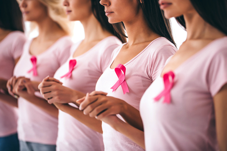 Cropped image of group of young multiracial woman with pink ribbons are struggling against cancer. Breast cancer awareness concept.