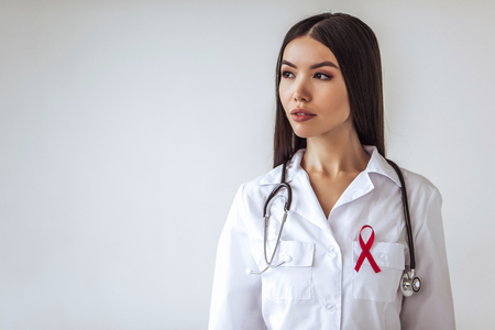 Atttractive asian female doctor with red ribbon is struggling against HIVAIDS. AIDS awareness concept.
