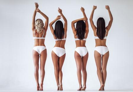 El grupo de mujeres multirraciales atractivas jovenes en la ropa interior blanca está presentando en el fondo blanco. Mujeres atractivas aisladas. Foto de archivo