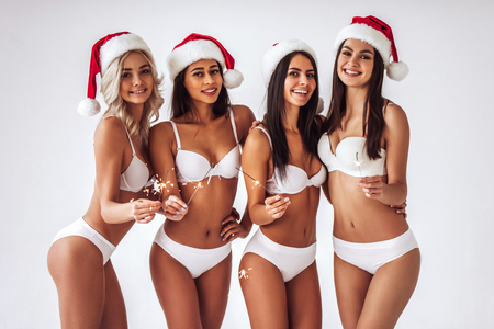 Group of young sexy multiracial woman in white lingerie are posing on white background in Santa Claus hats. Christmas and New Year celebration. Stock Photo