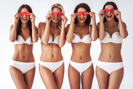 0a6bcd313b Group of young sexy multiracial women in white lingerie are posing on white  background with red