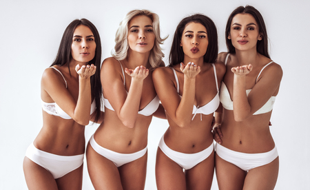 Group of young sexy multiracial women in white lingerie are posing on white background and giving air kisses. Attractive women isolated.