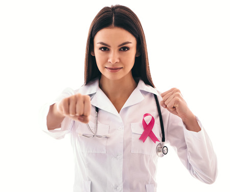 Atttractive young female doctor with pink ribbon is struggling against cancer. Breast cancer awareness concept.