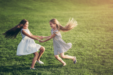 Little pretty girls having fun outdoor. Two cute girls are whirling on green grass. Best friends.