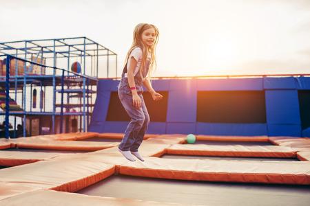 屋外で楽しい楽しみを持っている小さなかわいい女の子。子供ゾーンでトランポリンにジャンプ。 遊園