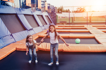 Little pretty girls having fun outdoor. Jumping on trampoline in children zone.  Amusement park 스톡 콘텐츠