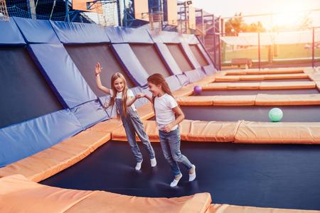 Little pretty girls having fun outdoor. Jumping on trampoline in children zone.  Amusement park Stock Photo