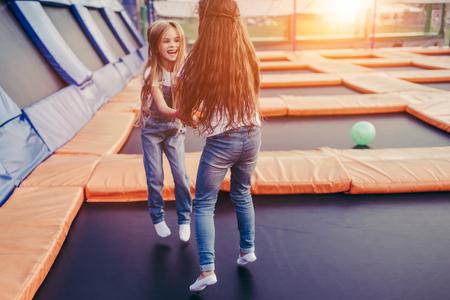 屋外で楽しい楽しみを持っている小さなかわいい女の子。子供ゾーンでトランポリンにジャンプ。遊園