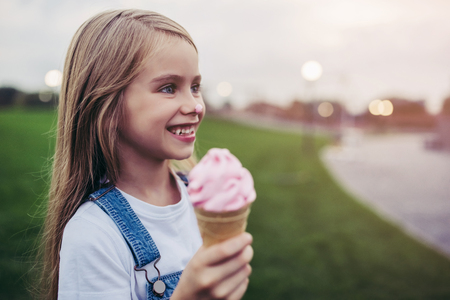 Little pretty girl is having fun outdoor. Standing on green grass and with ice cream in hands.