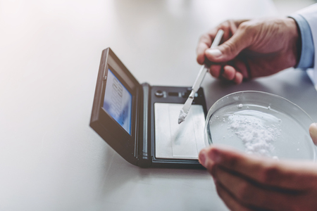 Scientist is working in laboratory. Lab researcher is doing investigations on laboratory equipment. Measuring the weight of component on laboratory weights.