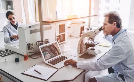 2人の科学者が研究室で働いている。若い女性研究者と上級指導教員が顕微鏡で調査を行っています。