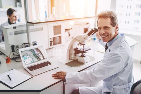 Dois cientistas estão trabalhando em laboratório. Jovem pesquisador feminino e seu supervisor sênior estão fazendo investigações com microscópio.